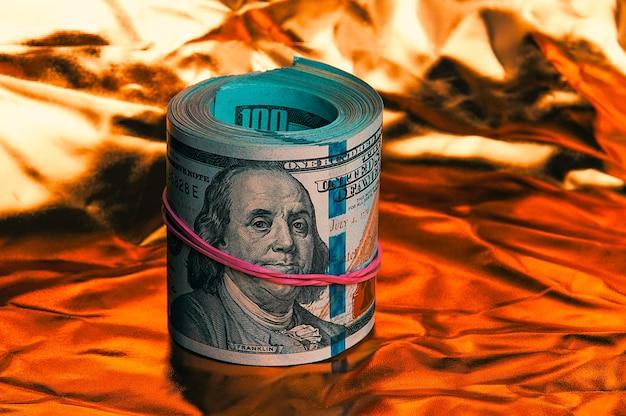 Een worp van honderd amerikaanse dollars in close-up op een gouden achtergrond