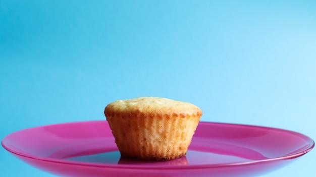 Een wrongelcake zonder poeder op een roze bord, op een blauwe achtergrond, zijaanzicht. kopieer de ruimte dessert, kleine cupcake, vers gebakken taart. voedselconcept. witgebakken koekjes met een luchtige structuur.