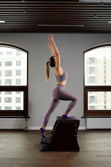 Een yoga-instructeur van een vrouw traint op een reformervat tegen het raam, correctie van het bewegingsapparaat op moderne reformerapparatuur, correctie van het bewegingsapparaat.