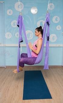 Een yogavrouw in een trainingspak zit in een hangmat in de studio