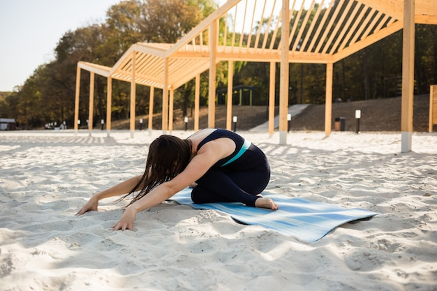 Een yogavrouw presteert op het strand