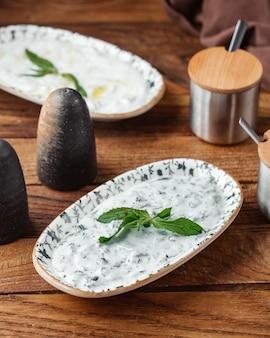 Een yoghurtmaaltijd van het bovenaanzicht met greens op het bruine houten de yoghurtvlees van het bureauvoedsel