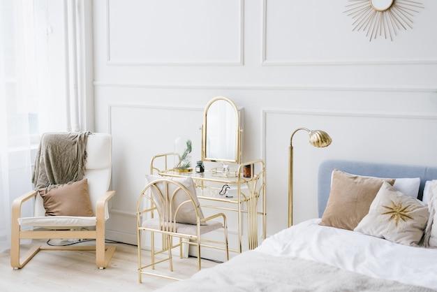 Een zacht lichte slaapkamer met een bed, stoel en boudoir-tafel bij het raam in scandinavisch