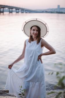 Een zacht portret van een charmante blanke vrouw in een witte zomerjurk en een strohoed die geniet van de...