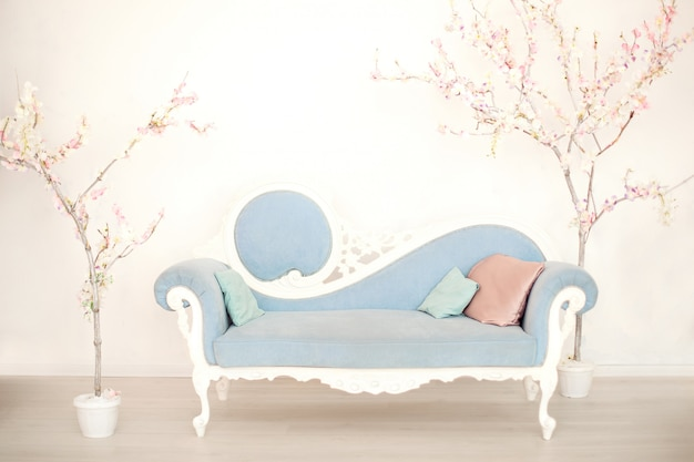 Een zachtblauwe bank met kunstbloeiende bomen in een witte woonkamer. bank in klassieke stijl in het huis. antieke houten fauteuil in vintage kamer. lente tijd! pastel kamer. woonkamer interieur