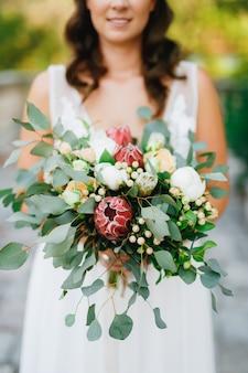 Een zachte bruid houdt in haar handen een ongebruikelijk huwelijksboeket van proteas van witte pioenenrozen en