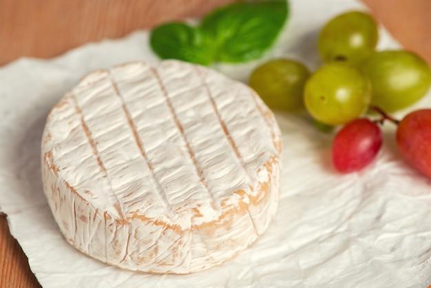 Een zachte gerijpte camembert-kaas en druiven op een witte achtergrond