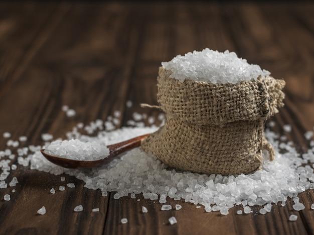 Een zak grof zout en een houten lepel op een rustieke tafel. gemalen steen zeezout.