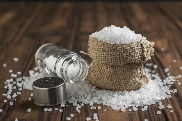 Een zak met verspreid zout en een glazen zoutvaatje op een houten tafel. gemalen steen zeezout.