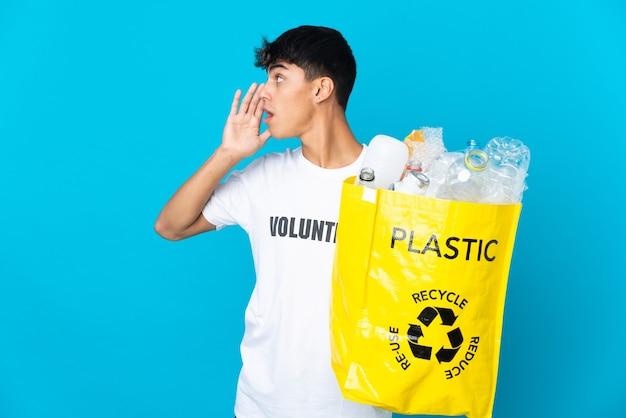 Een zak vol plastic flessen vasthouden om te recyclen op een blauwe achtergrond, schreeuwend met de mond wijd open aan de zijkant