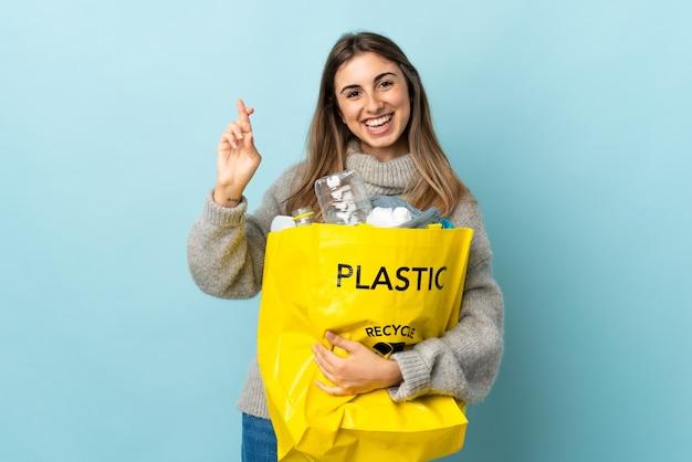 Een zak vol plastic flessen vasthouden om te recyclen op geïsoleerd blauw met gekruiste vingers