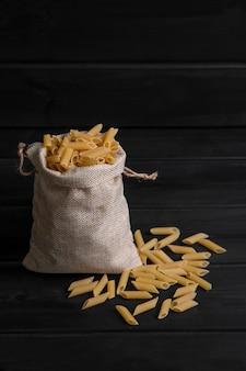 Een zak vol rauwe penne pasta op een donkere houten tafel. hoge kwaliteit foto