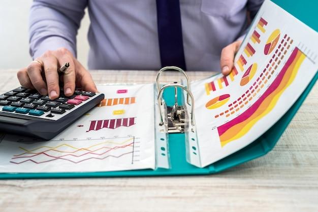 Een zakelijke man analyseert inkomsten en grafieken op kantoor. bedrijfsanalyse en strategieconcept. zakenman ontwikkelt een zakelijk project en analyseert marktinformatie, fotosessie van boven