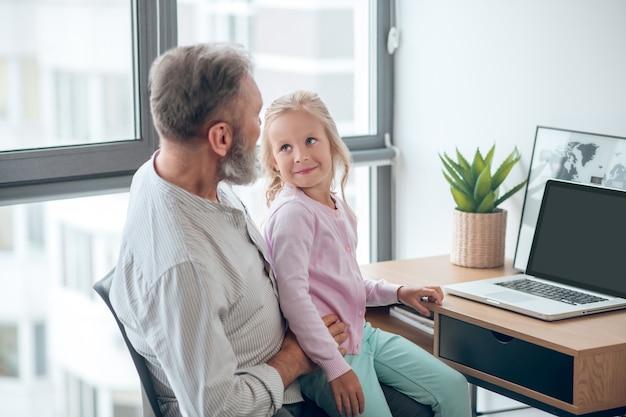 Een zakenman die aan tafel zit en zijn kleine dochter vasthoudt