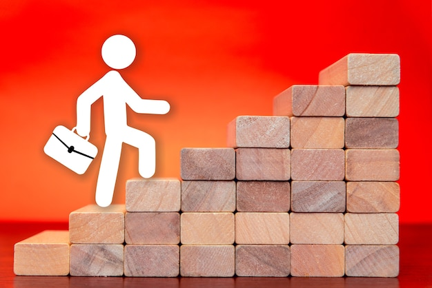 Een zakenman die de ladder opgaat naar succes in een conceptueel beeld op de rode achtergrond. de groei van een bedrijfsconcept en het pad naar succes.