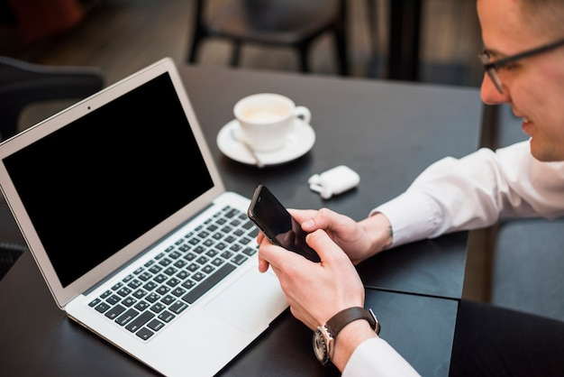 Een zakenman die de mobiele telefoon voor laptop met koffiekop op lijst met behulp van