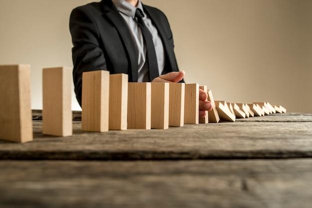 Een zakenman die een pak draagt en naast een reeks verticale houten platen staat die de een na de ander vallen. concept domino-effect waarbij één bedrijfsstoring verdere instortingen veroorzaakt.