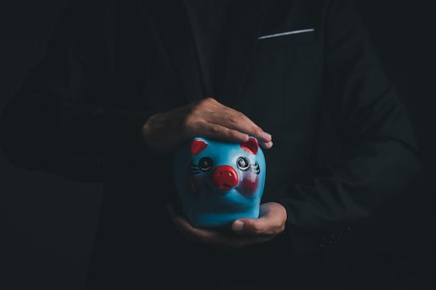 Een zakenman die het blauwe spaarvarken vasthoudt, close-up shot met kopieerruimte voor individuele tekst, spaar- en investeringsconcept