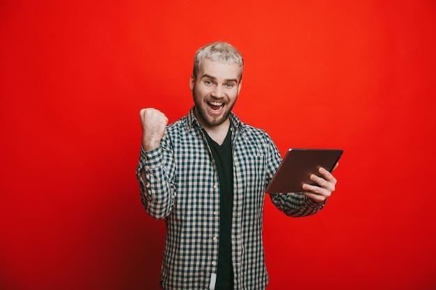 Een zakenman die zijn project had afgerond en nu wordt aangekondigd dat hij betaald krijgt voor poseren met een tafel op een rode achtergrond