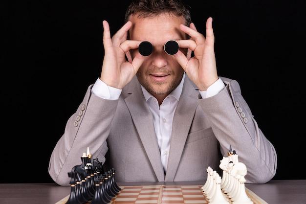 Een zakenman drukt emoties uit met zijn handen en zijn gezicht met schaakpionnen met humor