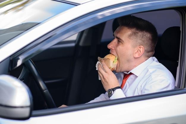 Een zakenman eet een hamburger in een auto.