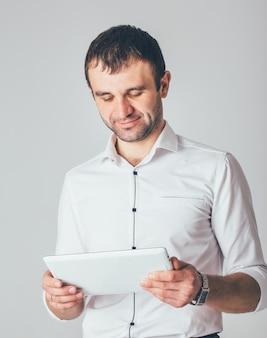 Een zakenman glimlacht en houdt een witte tablet in zijn handen. een man staat in een luxe shirt