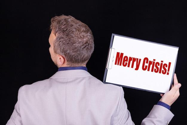 Een zakenman houdt een blanco vel papier met de tekst vrolijke crisis.