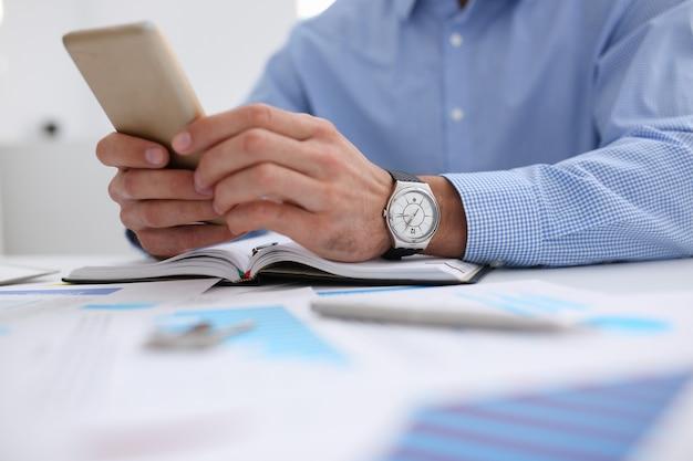 Een zakenman houdt een nieuwe smartphone in zijn hand