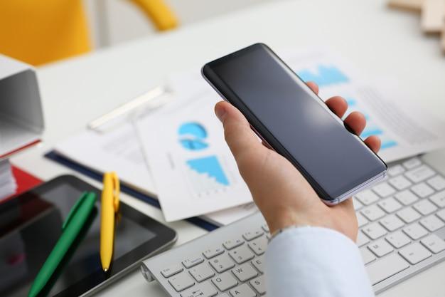 Een zakenman houdt een nieuwe smartphone in