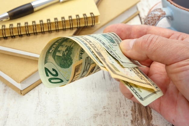 Een zakenman houdt verschillende dollarbiljetten in zijn hand. financieel begrip.