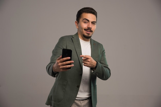 Een zakenman in dresscode die een smartphone promoot.