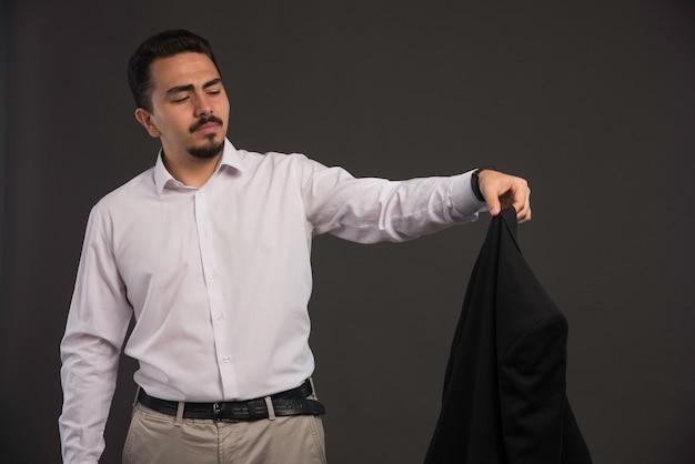Een zakenman in dresscode die een zwart jasje vasthoudt en ernaar kijkt.