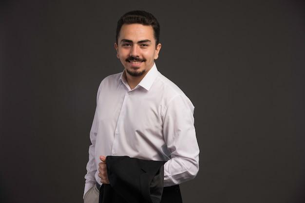 Een zakenman in dresscode met een zwart jasje in zijn arm.