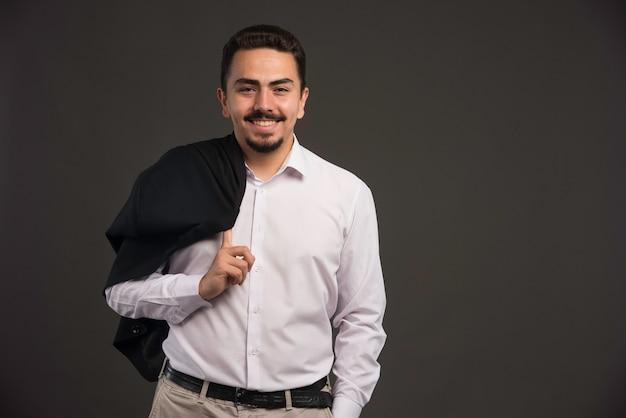 Een zakenman in dresscode met een zwart jasje in zijn schouder.