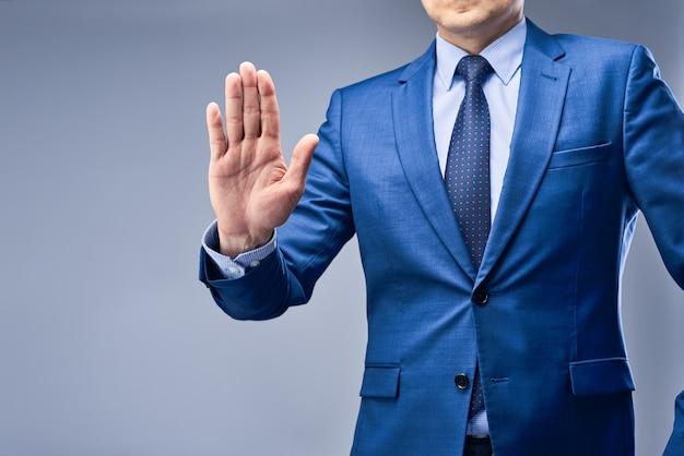 Een zakenman in een blauw pak houdt zijn hand voor hem