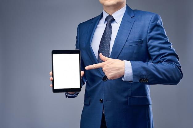 Een zakenman in een blauw pak met een tablet in zijn hand