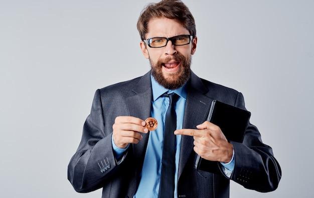 Een zakenman in een jasje houdt een cryptocurrency in zijn hand bitcoin-wisselkoersen. hoge kwaliteit foto