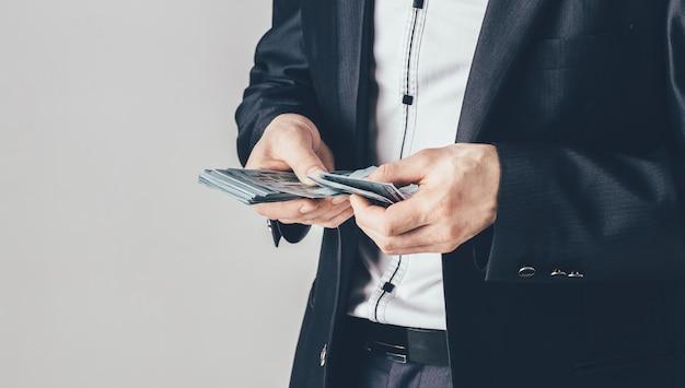 Een zakenman in een luxe zwart pak houdt dollars in zijn handen. de man telt zijn geld