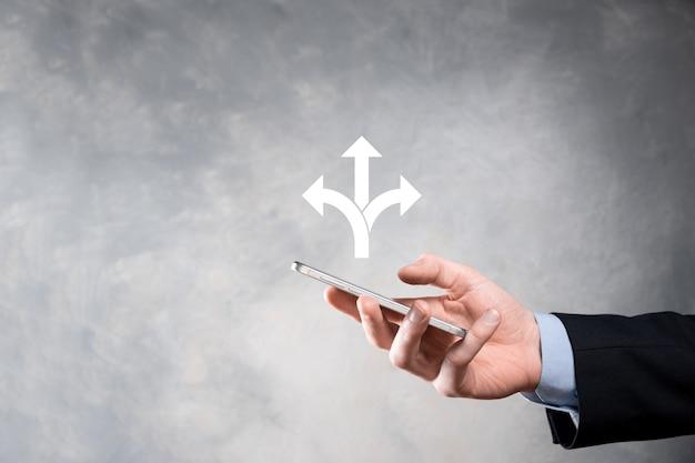 Een zakenman in een pak houdt een bord vast met drie richtingen die bij twijfel moeten kiezen tussen drie verschillende keuzes
