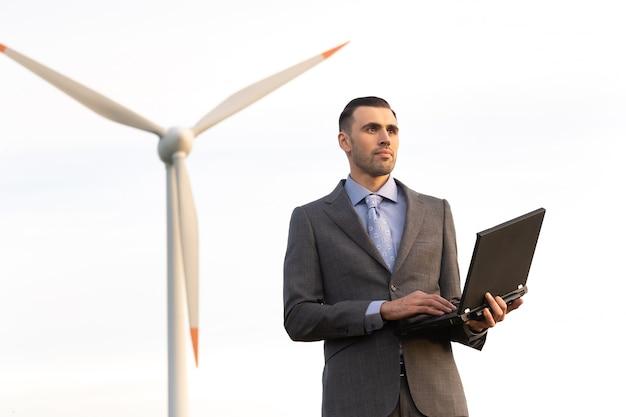 Een zakenman in een pak houdt een laptop in zijn handen tegen de achtergrond van een windmolen
