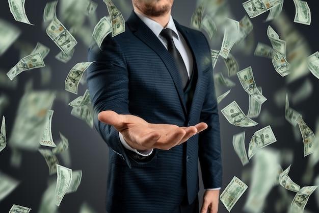 Een zakenman in een pak vangt de dalende dollars op. het concept van investeringen, dividenden, rente, bankdeposito's.
