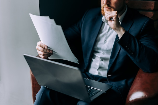 Een zakenman in een pak zit in een leunstoel met een laptop en analyseert informatie uit een paper.