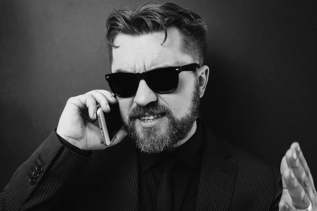 Een zakenman in een zwart pak zweert telefonisch.