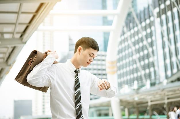 Een zakenman in wit overhemd gaat in spitsuren werken. hij kijkt op zijn horloge. hij wil op tijd naar kantoor.