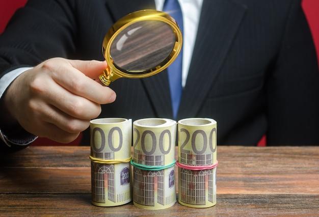 Een zakenman inspecteert een euro geld bundelt rollen door een vergrootglas