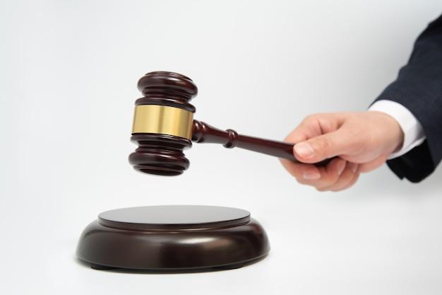 Een zakenman mannelijke hand houdt een houten rechtershamer die op wit wordt geïsoleerd