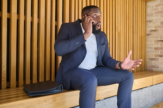 Een zakenman met een donkere huid die aan de telefoon praat en er betrokken uitziet