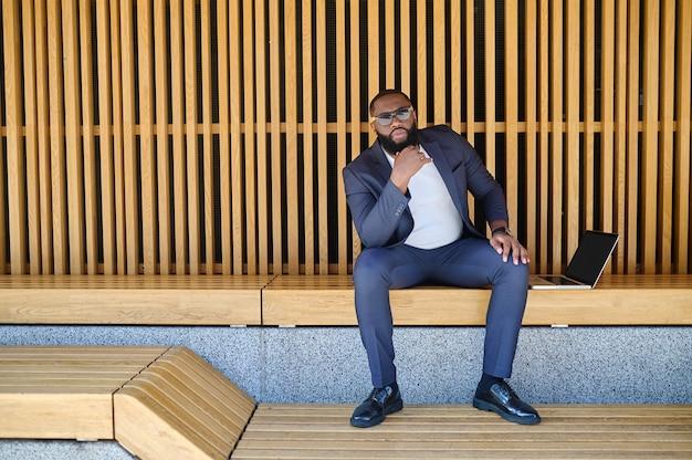 Een zakenman met een donkere huidskleur met een laptop zittend op de bank en aan het werk