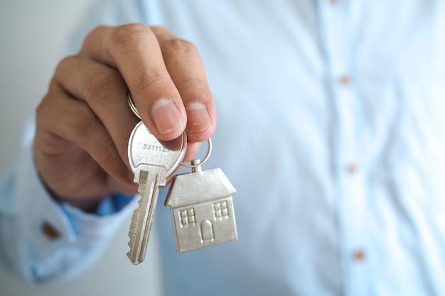 Een zakenman met een huissleutel. verkoop huis concept