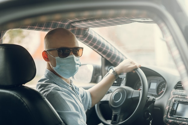 Een zakenman rijdt in een auto met een beschermend masker de bestuurder draagt een medisch masker
